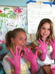 Wingspan Studio campers show off their pink hands during an art project.
