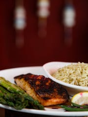 The blackened Atlantic salmon with rice pilaf and steamed vegetables at Waterfront Seafood Market in West Des Moines on Wednesday, May 18, 2016.