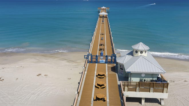 The Juno Beach Pier is deserted Wednesday after closing to slow the spread of the coronavirus.