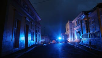 A police car patrols on a darkened street three weeks after Hurricane Maria hit the island, on Oct. 11, 2017, in Aibonito, Puerto Rico. The area is without running water or grid power as a nightly curfew remains in effect. Despite multiple visits from the Federal Emergency Management Agency, the town has yet to receive any FEMA aid.