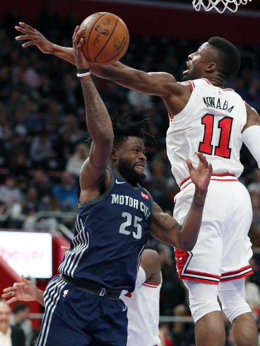 Detroit Pistons forward Reggie Bullock (25) passes as Chicago Bulls forward David Nwaba (11) defends during the first half of an NBA basketball game, Friday, March 9, 2018, in Detroit. (AP Photo/Carlos Osorio)