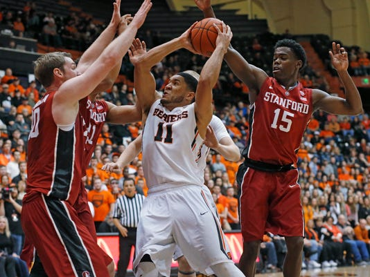 Oregon State's Malcolm Duvivier, center, drives on Stanford's Michael Humphrey, left, Cameron Walker, second from left, and Marcus Allen, right, during the first half of an NCAA college basketball game in Corvallis, Ore., on Wednesday, Jan. 6, 2016. (AP Photo/Timothy J. Gonzalez)