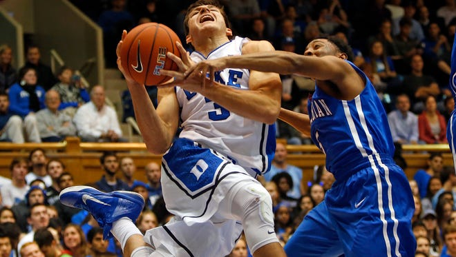 Duke's Grayson Allen, left,  drives the ball into Presbyterian's Davon Bell, right,  during the second half of an NCAA college basketball game in Durham, N.C., Friday, Nov. 14, 2014. Duke won 113-44.