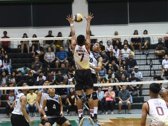 Tiyan High's Jericho Snaer attempts to get the kill on Father Duenas Friar Brnadon Mendiola (7) during their Independent Interscholastic Athletic Association of Guam Boys' Volleyball Championship game at the University of Guam Calvo Field House on May 12, 2018.