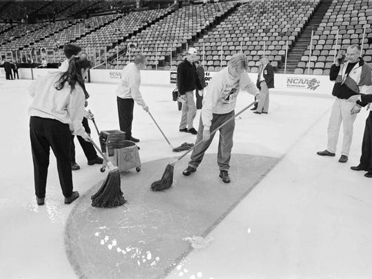 Workers clean up after a worker drilled into a line in the cooling system under the ice at Riverfront Coliseum on March 28, 1996, prior to the start of the Vermont-Colorado College Frozen Four semifinal game.