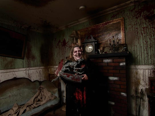 A haunted house actor prepares to scare guests at Frightland