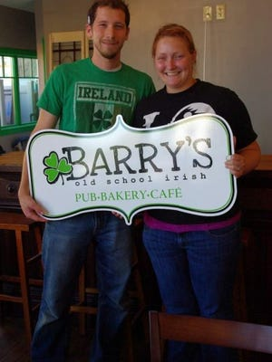 Danny and Jessica Barry pose with their new pub's sign a few days before opening in September 2011. (M. Rosenberry)