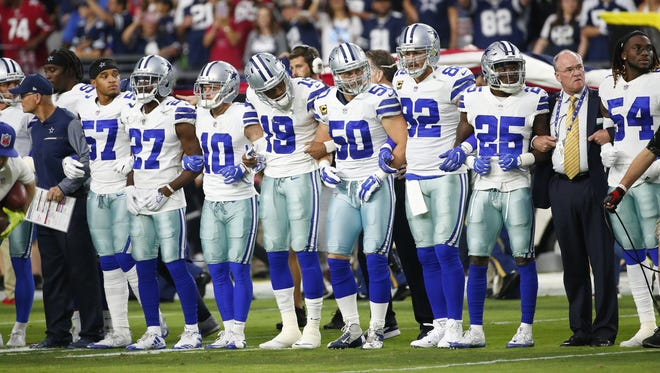 Dallas Cowboys players link arms before the National Anthem before Monday Night Football against the Cowboys at University of Phoenix Stadium in Glendale, Ariz. September 25, 2017.