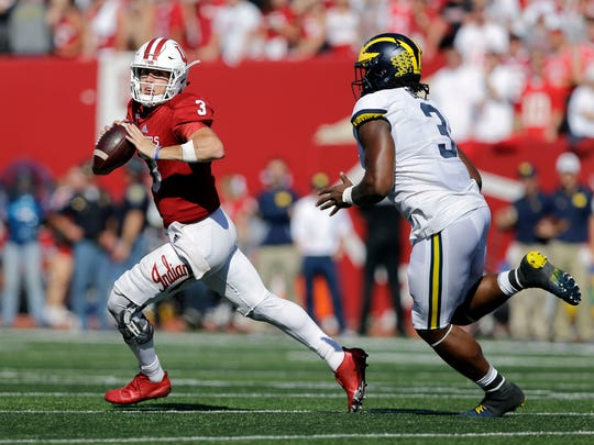 Indiana quarterback Peyton Ramsey, left, runs from Michigan defensive lineman Rashan Gary during the second half of an NCAA college football game in Bloomington, Ind., Saturday, Oct. 14, 2017. Michigan won 27-20 in overtime.