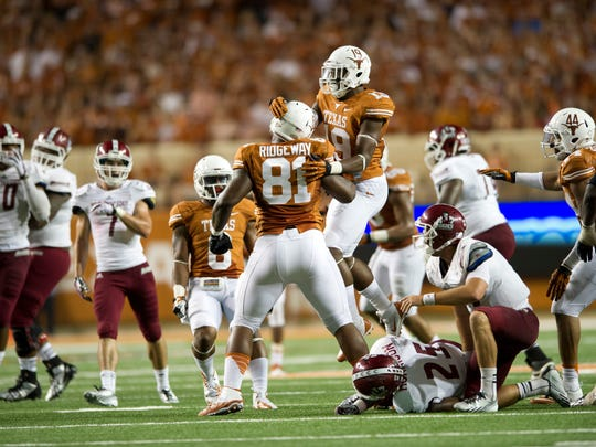 Hassan Ridgeway (81) celebrated with Texas Longhorn teammates after making a tackle for a loss of yards against the New Mexico State Aggies  in 2013.