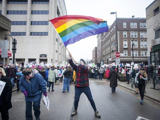Jamie Killips waves an LGBT pride flag on Jan. 21,