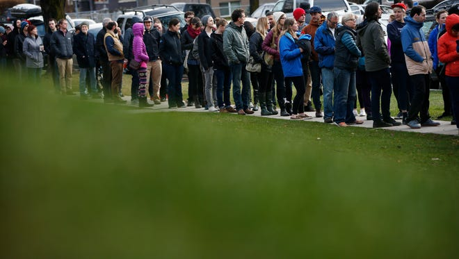 People wait in a line to vote at a Democratic caucus site Tuesday, March 22, 2016, in Salt Lake City.