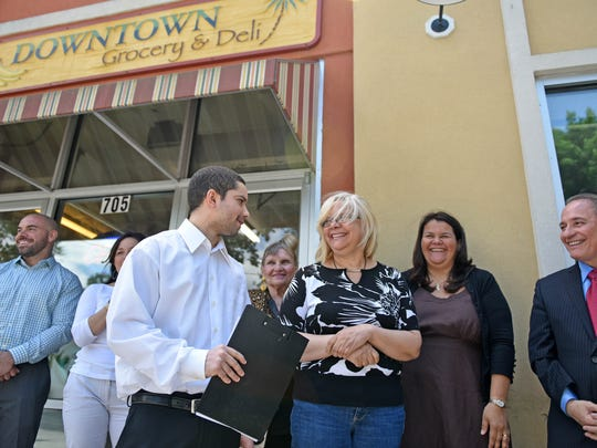 Adniel Carlos Rodriguez (center) and his mother, Dolores Rodriguez (right), owner of Downtown Grocery & Deli at Seventh and Wood streets in Vineland, are among the first store operators in Vineland to take part in the city's component of the New Jersey Healthy Corner Store Initiative. In background (L-R) are David Calderetti, Sara Paciocco, Pearl Giordano, Emma Lopez and Mayor Ruben Bermudez.