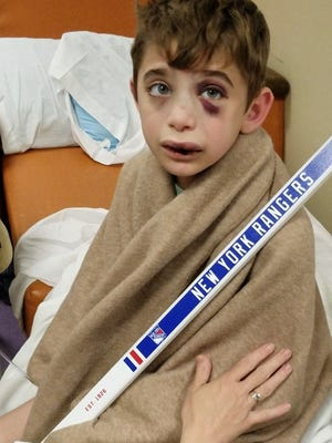 Brendan O'Callaghan in his hospital bed with the signed New York Rangers goalie stick he received.