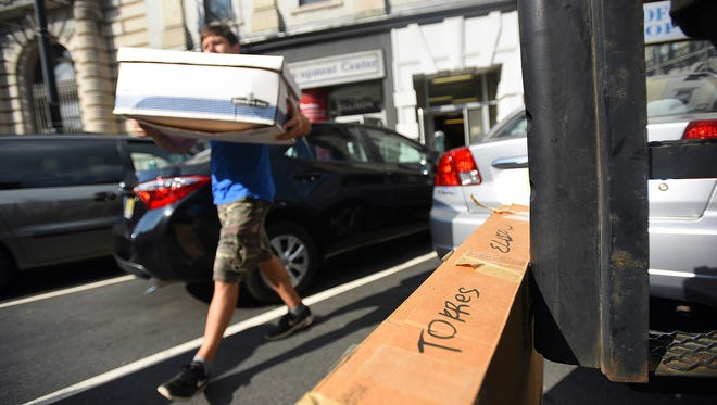 A box bearing the name of the former Paterson mayor leans against a moving company truck as a worker carries a crate from the city Division of Recreation building on Monday.