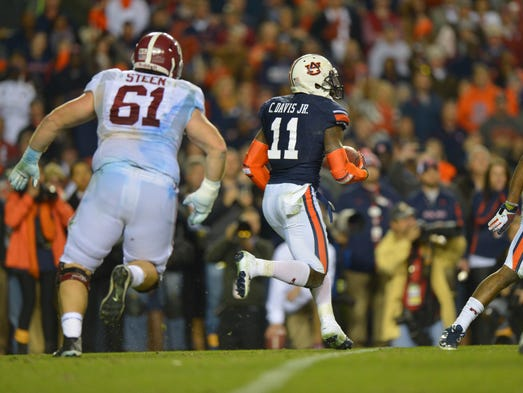 Auburn cornerback Chris Davis returns a missed field goal 108 yards with no time left to secure a 38-34 victory for the Tigers. Alabama Crimson offensive linesman Anthony Steen gives chase.