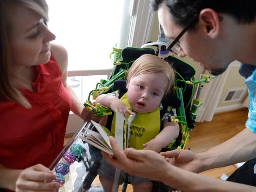 Kristen and Jonathan Lasko play with their 13-month-old son, Max, at their house in Derwood, Md. Max was born with spinal muscular atrophy, a genetic disorder that causes muscle weakness so severe that he cannot breathe on his own. He uses a Wilmington Robotic EXoskeleton to help him with movement.