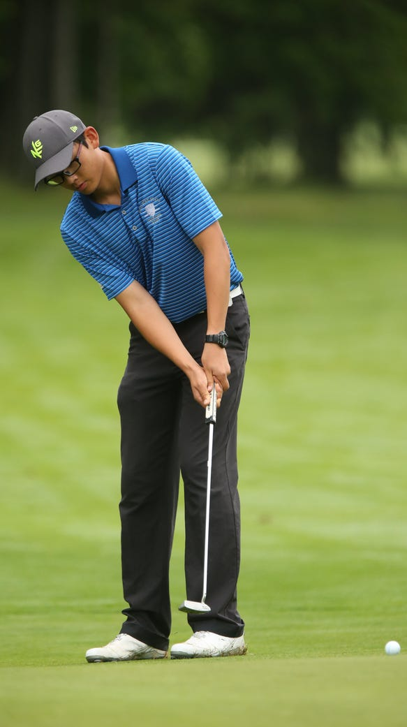 Section 1's Andy Fan putts his ball on the 7th green