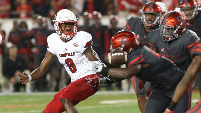 U of L QB Lamar Jackson (8) loses control of the ball against the defense of Houston's Steven Taylor (41), a play that led to a turnover. Nov. 17, 2016