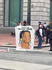 A man holds up an illustration of Aiyana Jones, a Detroit