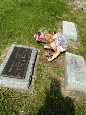 Hana Mackey, 5, places American flags on the graves of veterans at the Grinnell cemetery Memorial Day 2014.