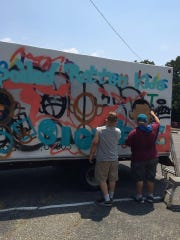 Leon Rainbow and Michael Dybus, two graffiti artists, paint over an old spray paint tag on the side of Spoiled Rotten Kids Consignment truck in Barnegat.