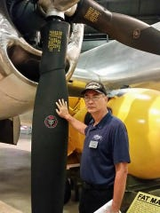 """James Belcher Jr. at the Air Force Museum in Dayton, Ohio. His hand touches Bockscar, the plane that dropped the bomb on Nagasaki. """"This was the first time I ever felt an actual presence of my Japanese grandfather,"""" said Belcher Jr. """"I was emotionally overwhelmed."""""""