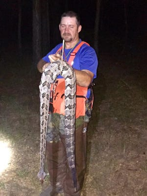 Brad Goodman holds a 5-foot rattlesnake he and Daniel Sims killed while hunting raccoons Sunday night.