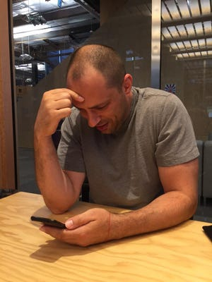 WhatsApp founder Jan Koum  photographed by Facebook CEO Mark Zuckerberg as he announces that WhatsApp has hit 900 million monthly active users.