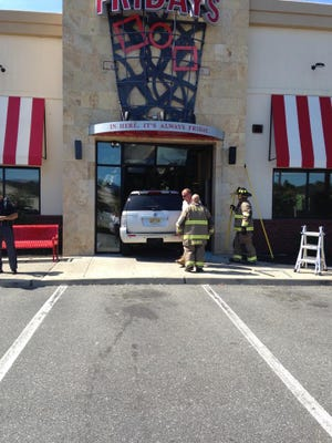 Firefighters surround the silver Mercury Mountaineer that crashed into the TGI Friday's vestibule Wednesday in Manahawkin. Firefighters helped the driver escape the car from the rear hatch.