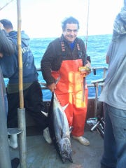 An angler holds a longfin tuna he caught on the 125-foot