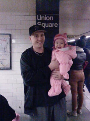 Brian Weldon, Molly's father, holds her at seven months in a Manhattan subway station.