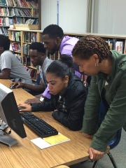 Students and mentors at Delcastle Technical High School work on college applications.