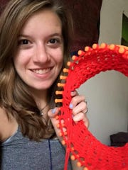 Emily Kubin works with a hat loom to knit a red winter hat.