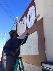 A fresh layer of paint is applied to the building that used to house a pool hall but which is slated to become the resource center for  the new Carlsbad Community of Hope, a tent city that could house up to 50 of Carlsbad's homeless.