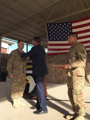 Defense Secretary Ash Carter, center, pins the new Operation Inherent Resolve campaign medal on Sgt. Curtis Bluel on Monday in Iraq. Bluel was one of two soldiers this week to be the first awarded with the new campaign medal.