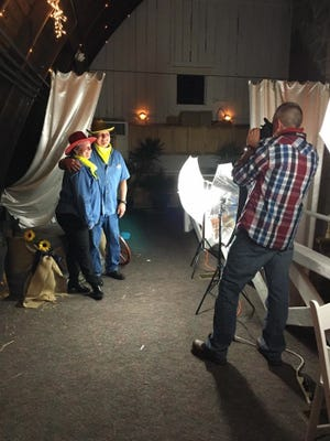 """Tom Robinson, right, gets a picture of Dawn and Tom Urbany in their """"Hoedown"""" garb Saturday night at the Corporate Development Campaign's annual dance."""
