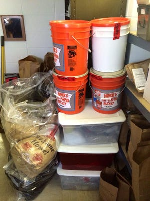 Marijuana seized from suspected smugglers sits in buckets and plastic totes inside an evidence room at the Deuel County Sheriff's Office in Nebraska. Deputies there say they've seen a surge in Colorado marijuana flowing through their state.