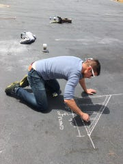 """Dan Sullivan, the lead artist on the """"Catacomb of Veils"""" project, sketches plans with chalk at the build site in San Francisco."""