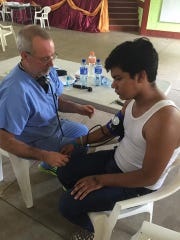 Brian Beck (left) meets with a patient in a clinic in León, Nicaragua, in June.