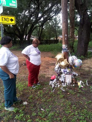 PAIN members at a makeshift memorial in Pensacola. PAIN is breaking ground July 13 on a memorial garden where families can mourn loved ones who were lost to violence.
