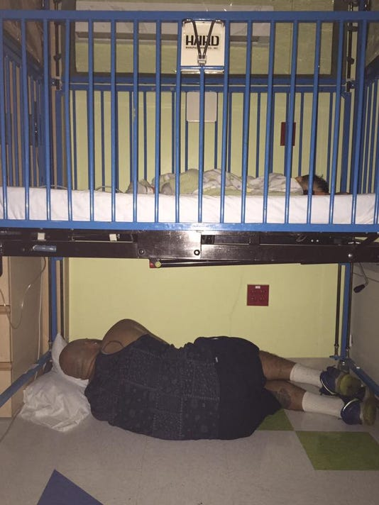 Dad sleeps under son's crib