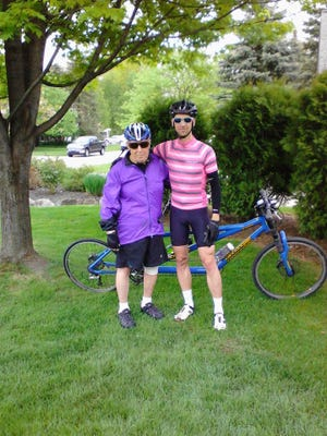 Jim Healy (left), who is totally blind, took a practice ride on a tandem mountain bike with his nephew Tim Saari (right) in May. The men have been training for a 100-mile bicycle ride in the 2016 Susan G. Komen Mid-Michigan Ride of the Cure to raise money for the fight against cancer.