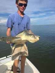 Will Mercer holds up the sea turtle whose life he helped save. Lacerations caused by fishing wire can be seen around its neck.