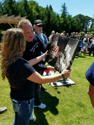 Trina Hart looks at an enhanced photo of her son's casket, presented by the Tribute to Fallen Soldiers Northwest motorcycle riders.