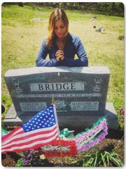 Amanda Bridge at the headstone of her father, who died of a heroin overdose.