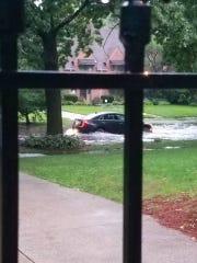 A motorist encounters some flooding along Iroquois