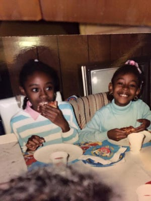 Jennifer Wade, right, with her sister, Sheneeka, at a birthday party in their house in Kalamazoo, Mich., in the 1980s