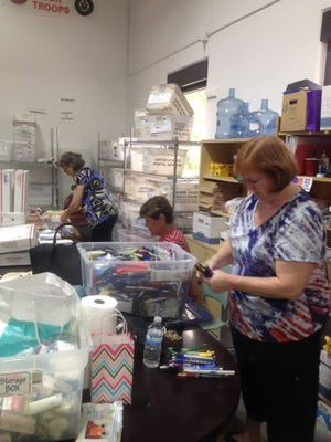 Volunteers sort and pack items for care packages that are sent each month to active duty, overseas military personnel.