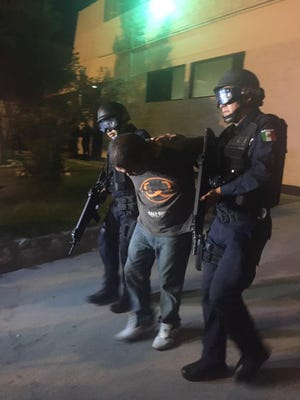 Juárez police escort a man arrested in connection with a fatal shooting Tuesday night in La Cuesta area.